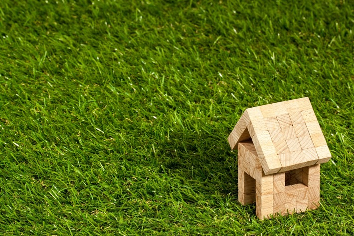 A small wooden toy house sits on a patch of bright green grass.